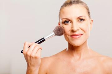 beautiful mature woman applying make up