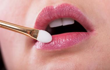 Young Woman Applying Make-up On Lips