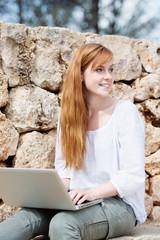 junge frau sitzt draußen mit laptop