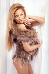Sensual blonde woman posing in fur