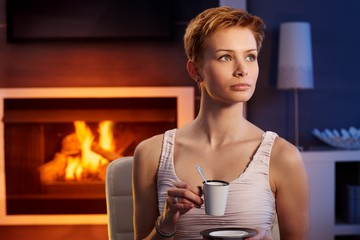 Beautiful woman having coffee in cosy room