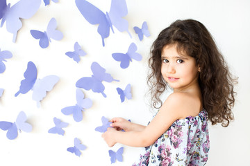 The girl against a wall decorated with butterfly