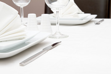 Place setting with white plates and wine glasses