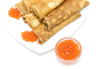 red salmon caviar and crepes on a plate on a white background