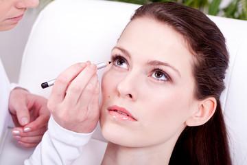 junge brünette frau wird im kosmetikstudio geschminkt Nahaufnah