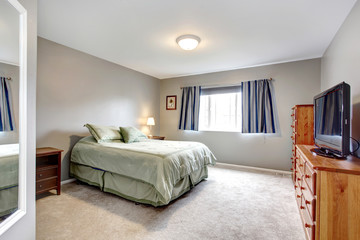 Large grey bedroom with dresser, tv and blue curtains.