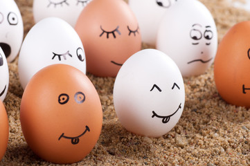 group of Funny crazy smiling eggs on a sand