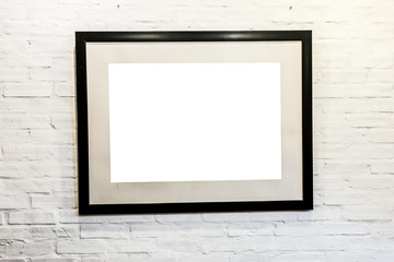 Black frame with blank space on brick wall.