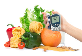 Diabetes concept glucose meter in hand fruits, vegetables
