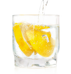 A glass of cold drink with a lemon from the fridge. On a white b