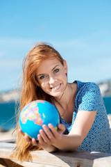 lachende junge frau mit globus am meer
