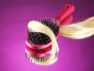 Comb brush with hair on purple background