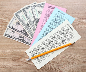Lottery tickets with pencil and money, on wooden background