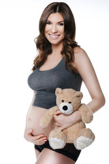 Beautiful smiling pregnant woman with plush toy