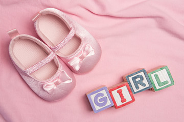 Pink baby slippers and blocks spelling girl