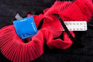 Detailaufnahme eines Strapsgurtes mit Kondom und Pillenpackung