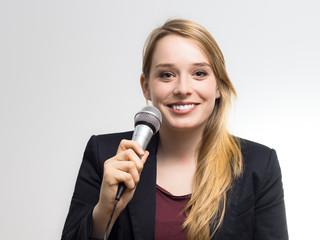 Junge Frau singt ins Mikrofon