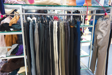 shop pants different group colored jeans hanging on a hanger in