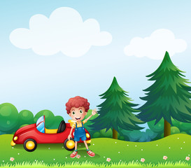A young boy beside his car at the hill