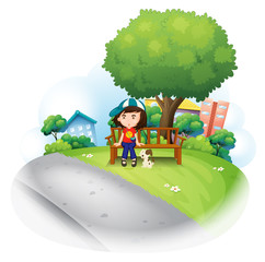 A girl sitting at the wooden bench near the big tree