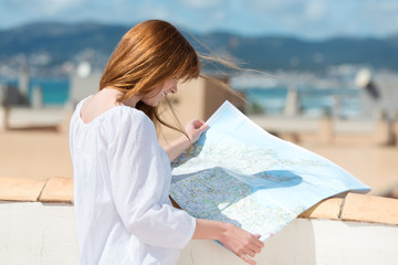 frau im urlaub schaut auf landkarte