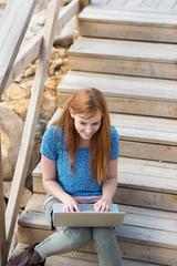 mädchen sitzt draußen mit laptop