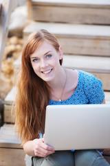 lächelndes mädchen mit laptop
