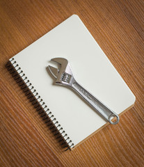 Notepad and Adjustable Wrench