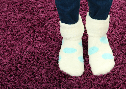 Female legs in colorful socks on color carpet background