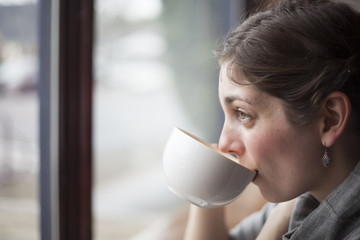 Beautiful Young Woman Holding Her Morning Cup of Coffee