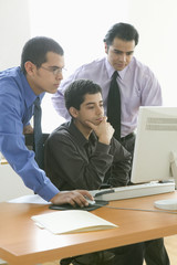 Three businessmen looking at computer screen