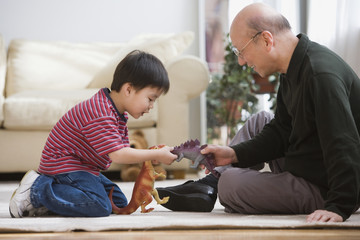 Elderly man and grandson playing with toy dinosaurs