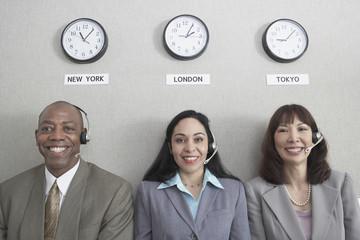 Three businesspeople under world time zone clocks