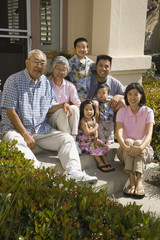 Multi-generational Asian family smiling on front steps of house