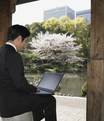 Asian businessman using laptop in urban park
