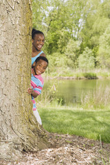 African sister and brother peeking out from behind tree in park