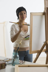 Hispanic woman painting on easel