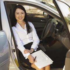 Eurasian businesswoman sitting in car
