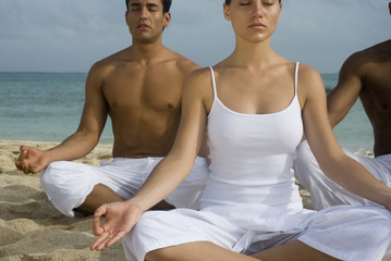 Multi-ethnic friends meditating on beach