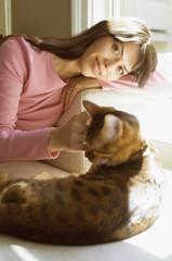 Hispanic woman petting cat