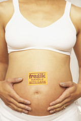 Pregnant Mixed Race woman with fragile sticker on belly