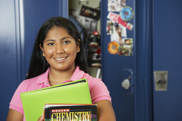 Hispanic teenaged girl in front of school locker