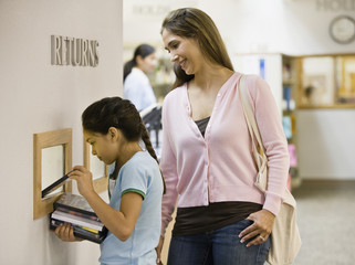 Mixed Race mother and daughter returning library books