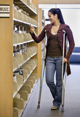 Hispanic woman in crutches in library