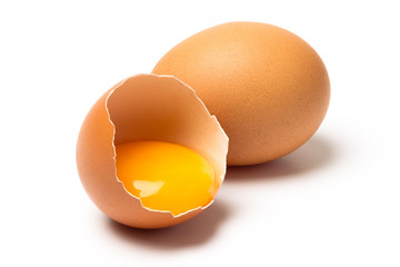 Two eggs, one broken, with shadow isolated on white background