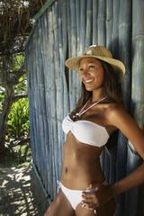 Hispanic woman in bikini leaning against bamboo