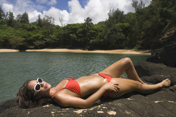 Pacific Islander woman sunbathing on rocks next to water