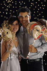 Hispanic couple dressed for night out with ornate masks