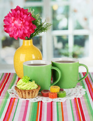 Cups of tea with cake,candy and flower on table in room