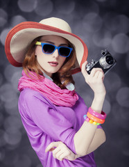 Funny redhead girl in hat with camera and bokeh at background